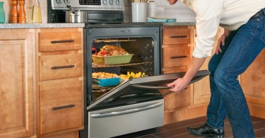 Man opening oven full of food