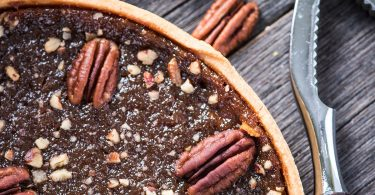 Pecan pie, nut crusher on table from above