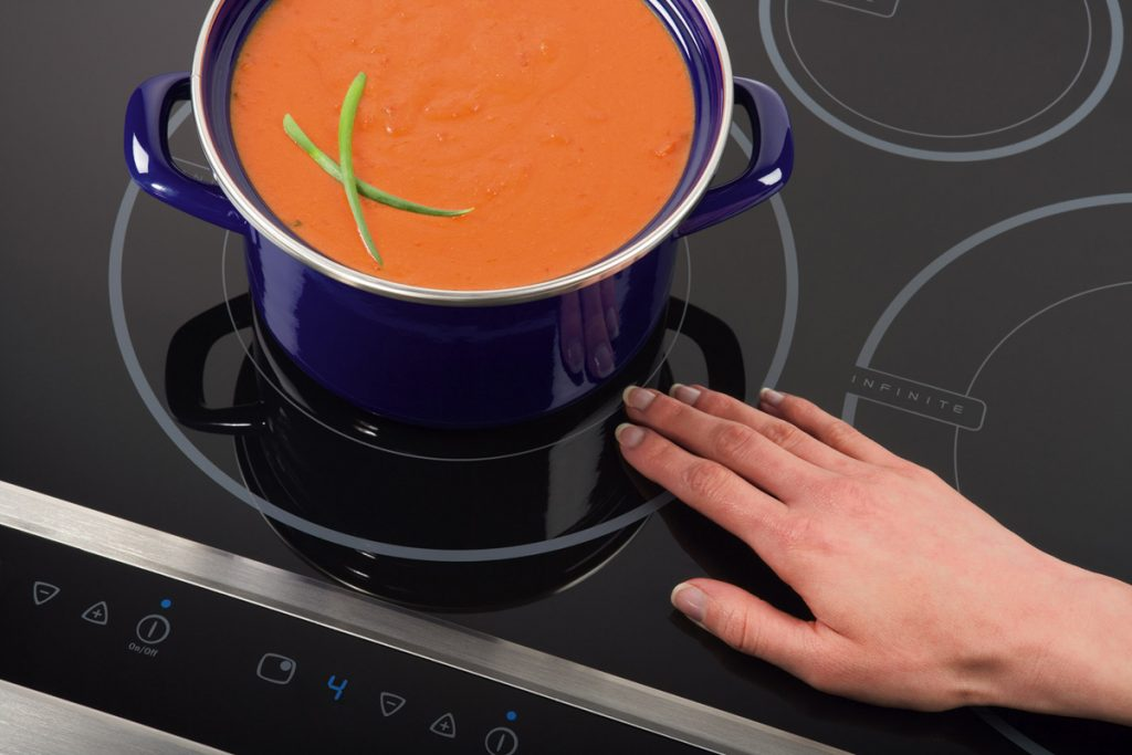Hand resting near burner of Electrolux induction cooktop