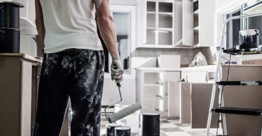 Man with paint roller in kitchen painting cabinets