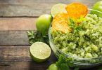 Roasted Salsa Verde in a bowl on wooden table with lime and tomatillos around