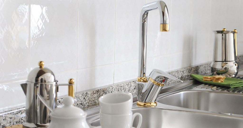 kitchen sink faucet trimmed in gold
