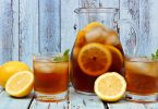 Pitcher of iced fruit tea with two glasses on rustic blue wood
