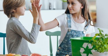Siblings giving high five in the kitchen