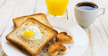 Egg fried in a heart-shaped toast cutout sprinkled with cracked pepper and rosemary, orange juice and cup of espresso. Wooden table. Selective focus