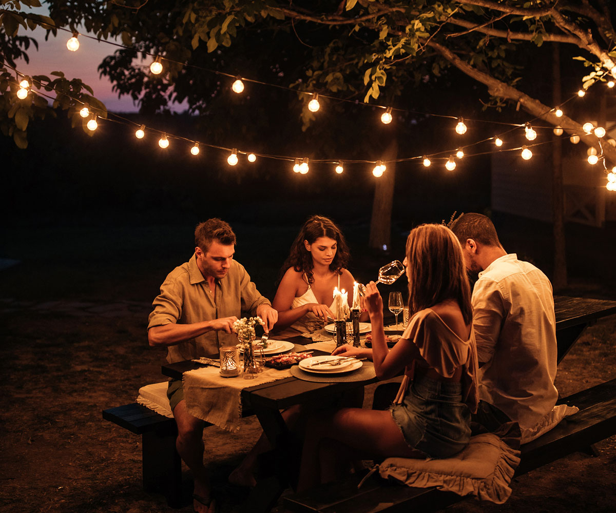 Two couples having a dinner party in a backyard