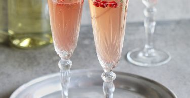 Pomegranate champagne in glasses on a tray