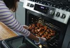 Women taking buffalo wings from Frigidaire range with air fry