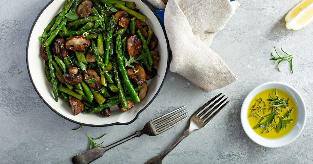 Asparagus and mushrooms sauteed in a cast iron pan