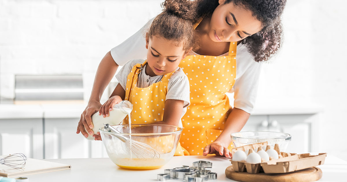 mother and daughter preparing dough and pouring milk into bowl