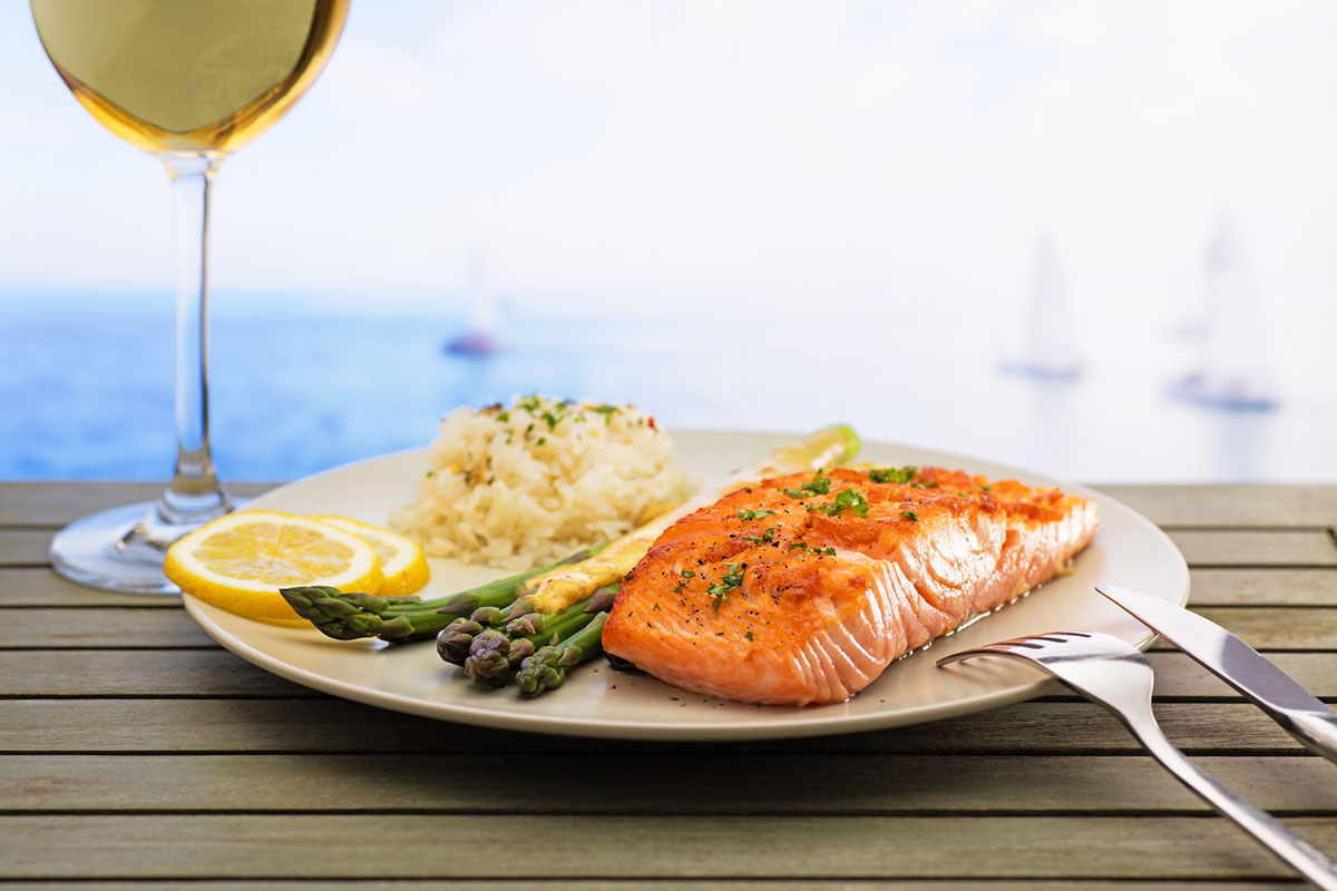 Salmon with asparagus and rice, freshly served with a glass of wine.