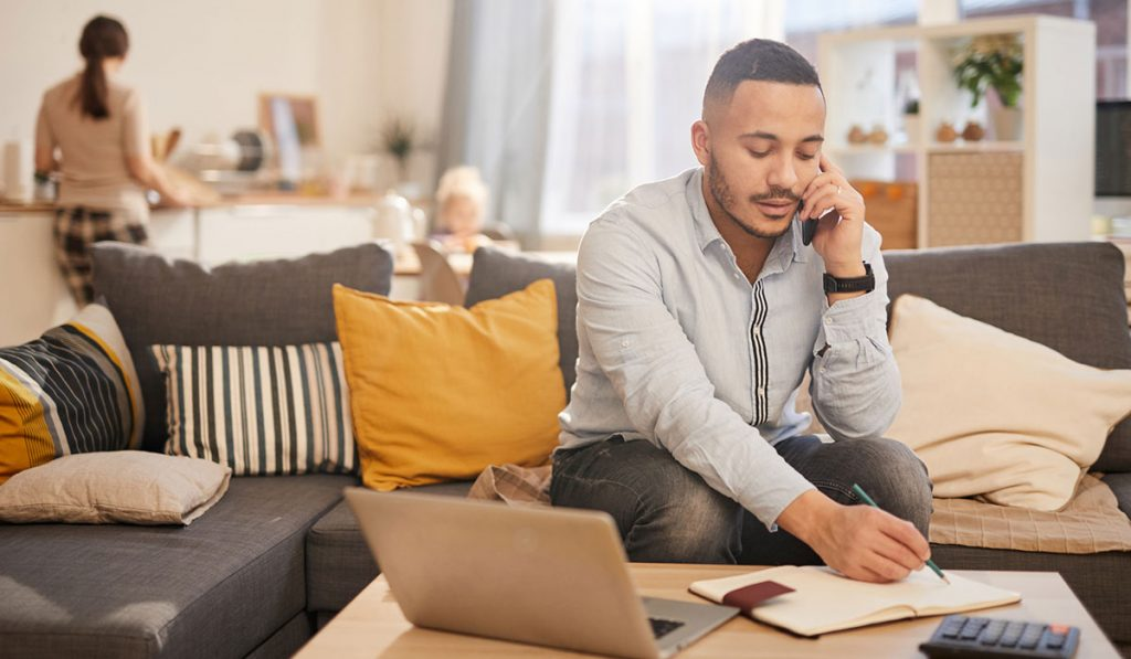 Man working from home, family in the kitchen behind him