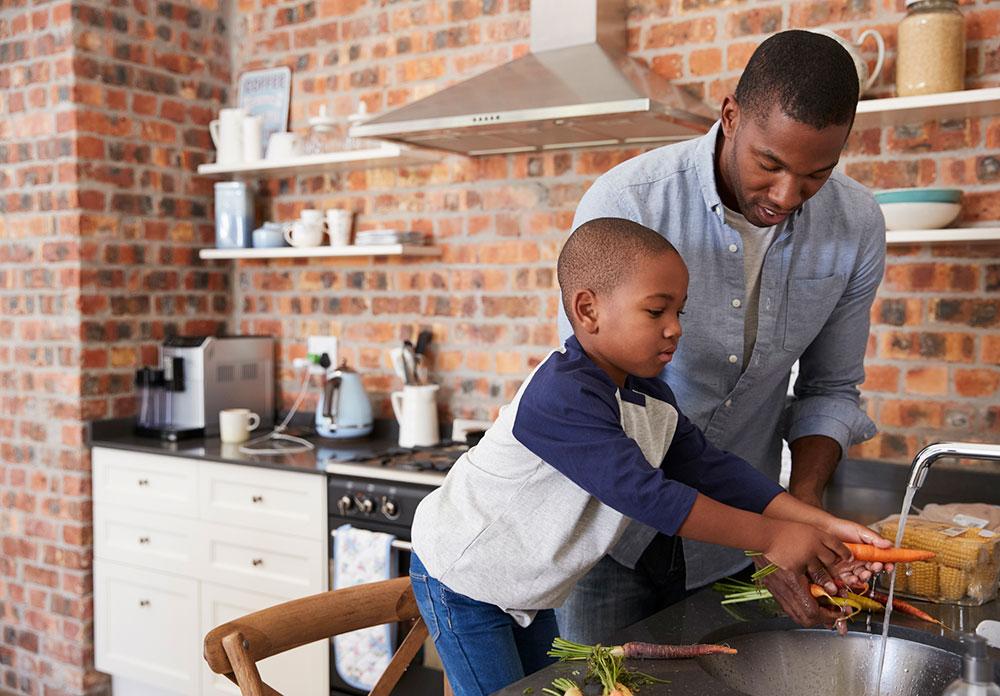 Boy helping dad wash vegetables