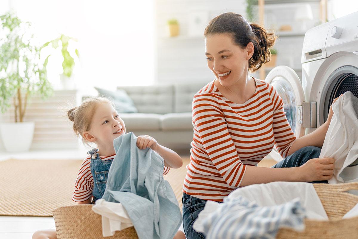 girl helping mom fold laundry